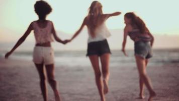 niñas corriendo y tomados de la mano en una playa al atardecer