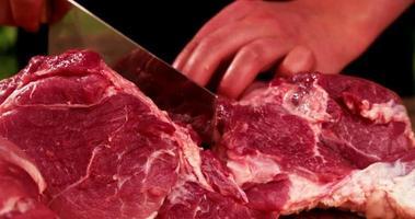 großes Stück rohes Schweinefleisch wird mit einem Hackmesser geschnitten
