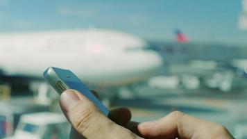 Geschäftsmann benutzt das Smartphone am Flughafen. Hände eines Mannes mit dem Telefon im Hintergrund des Flugplatzes und des Flugzeugs