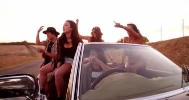 Amigos boho adolescentes sentados en un capó convertible al atardecer
