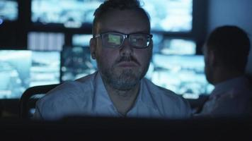 Focused security officer is working on a computer in a dark monitoring room filled with display screens.