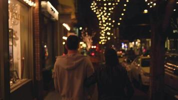 una giovane coppia che cammina di notte lungo un marciapiede della città