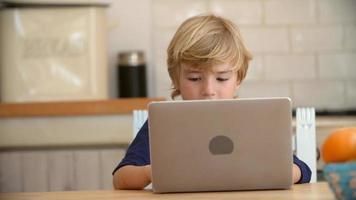 giovane ragazzo utilizzando il computer portatile al tavolo della cucina, da vicino