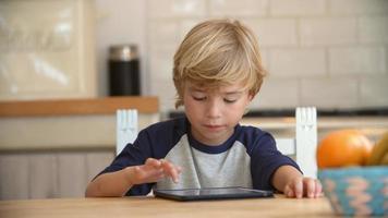 Junge mit Tablet-Computer am Küchentisch, Pfanne