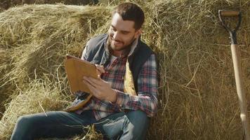agricultor está sentado no feno e usando um computador tablet. video