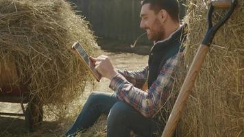 homem está sentado no feno e usando um computador tablet. video
