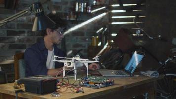 l'uomo sta saldando componenti elettrici su un drone in un garage mentre controlla un computer portatile. video