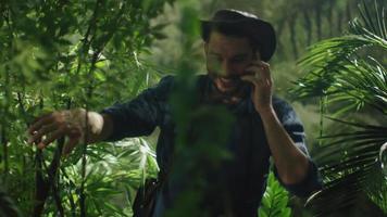 aventureiro no chapéu usando falando no celular na floresta da selva.