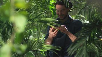 aventureiro de chapéu usando telefone celular na floresta da selva.