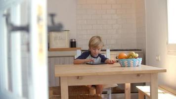 giovane ragazzo utilizzando computer tablet in cucina, dalla porta