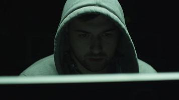 riprese ritratto di impiegato maschio concentrato che indossa un cappuccio e lavora su un computer in una stanza buia dell'ufficio.
