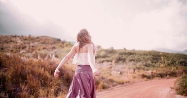 garota boho em uma estrada de terra sendo alegre
