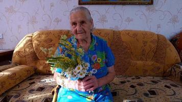 velha sentada em um sofá em seu apartamento. ela segura flores nas mãos
