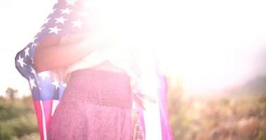 ragazza con la bandiera americana sulle spalle nel paesaggio naturale