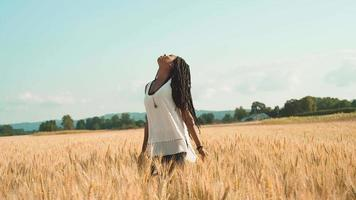 hermosa mujer negra jugando en un campo de trigo