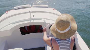 empuriabrava, spagna: donna turista nuota guidando barche a motore attraverso il canale. vacanza in europa, tour in mare. colpo steadicam