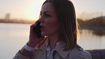 mujer hablando por teléfono al atardecer