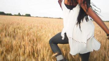 hermosa mujer negra corriendo por un campo de trigo