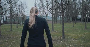 achteraanzicht van een geschikte vrouw buiten in een park