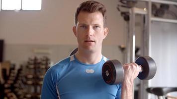 Hombre trabajando con pesas en un gimnasio, vista frontal de cerca