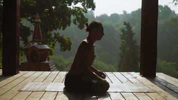 yogi seduto nella posizione del loto ed esegue la torsione