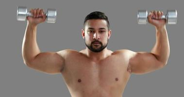 Hombre musculoso serio levantando pesas video