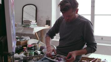 Artista poniendo pintura al óleo en la paleta en foto de estudio en r3d