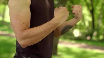 Man doing fitness exercise outdoor. Close up of fitness man stretching wrist