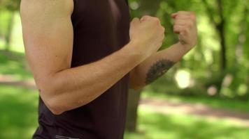 uomo che fa esercizio di fitness all'aperto. Close up fitness uomo che allunga il polso