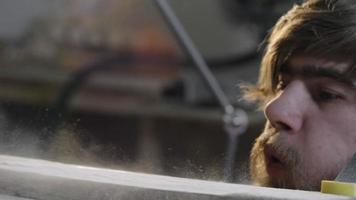 falegname che soffia via la polvere di legno