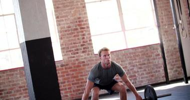 Joven levantando pesas durante el entrenamiento de gimnasia en el gimnasio video