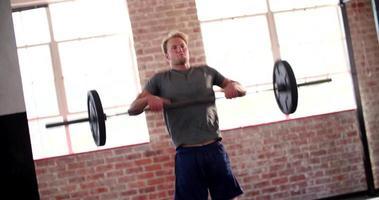 giovane che fa esercizio pulito di potere durante l'allenamento in palestra