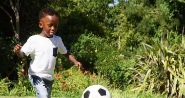 kleiner Junge, der im Fußball schießt