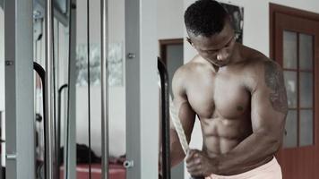 Hombre atlético entrenamiento en máquina de fitness video