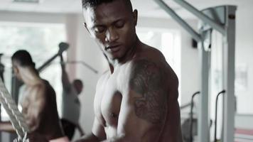El hombre ejecuta el ejercicio de tríceps en la máquina de cable video