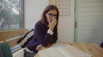 linda aluna de óculos estudando à mesa com livros
