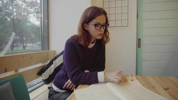 jovem estudante universitária caucasiana fazendo lição de casa e tomando notas no livro video