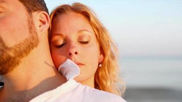 um casal se abraçando na praia ao pôr do sol video