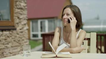 fille parlant au téléphone et lisant un livre
