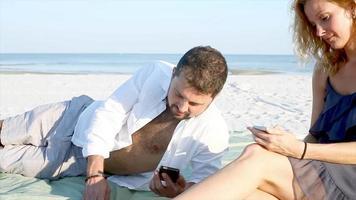 um casal sentado na praia usando seus telefones celulares video