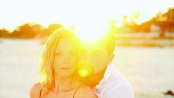 pareja abrazada en la playa al atardecer video