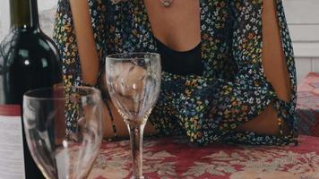 loira conversando à mesa com uma garrafa de vinho tinto no terraço de uma casa de campo