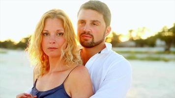 um casal se abraçando na praia ao pôr do sol