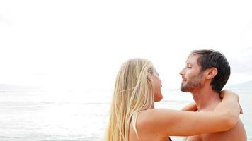 casal se abraça perto do oceano