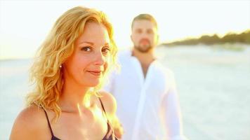 um casal brincando na praia ao pôr do sol