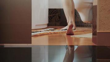 femme aux jambes nues marche dans la salle de bain et reste aux toilettes. remettre les sous-vêtements