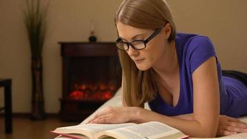 Hermosa mujer joven con gafas acostado en un sofá, leyendo un libro