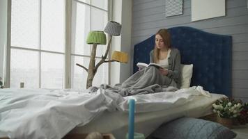 bionda che legge un libro mentre era seduto a letto