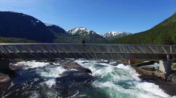 Mädchen auf der Brücke beobachtet Wasserfall