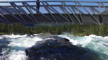 voo sob a ponte acima da cachoeira na Noruega